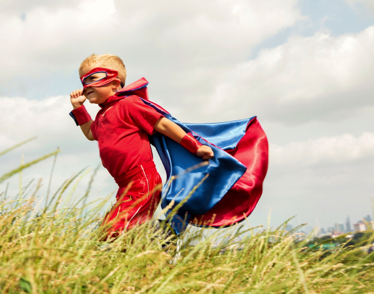 Little boy running in superhero costume